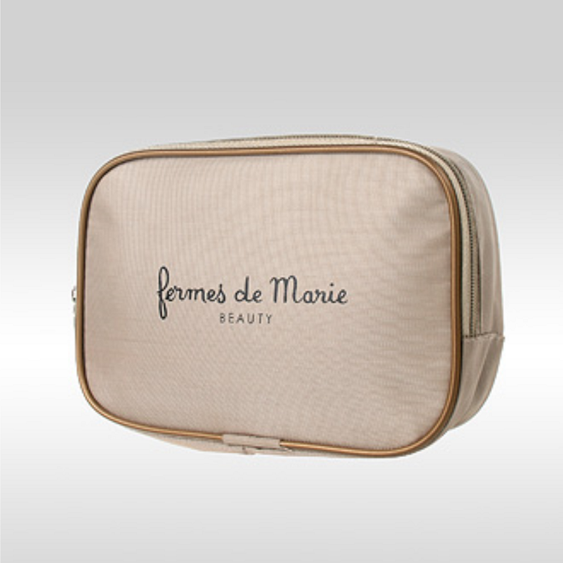 Фото золотистой косметички из ткани оксфорд с логотипом Fermes de Marie Beauty